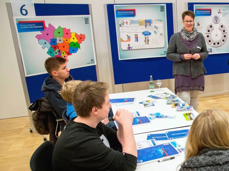 Eine Frau steht vor Schülerinnen und Schülern, die an Tischen sitzen. Hinter ihr hängen Karten und Schautafeln an Ausstellungstafeln.