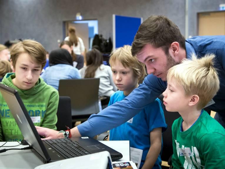 Vier Personen scharen sich um einen Laptop und schauen auf den Bildschirm.