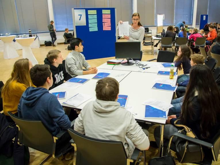 Blick auf eine Gruppe von Schülerinnen und Schülern, die an mehreren zusammengeschobenen Tischen sitzen und einer Frau zuhören.