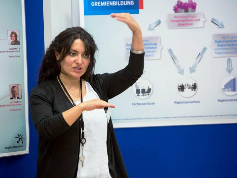 Eine Frau steht vor Schautafeln und trägt etwas vor, ihre Händen zeigen dabei etwas in der Luft.