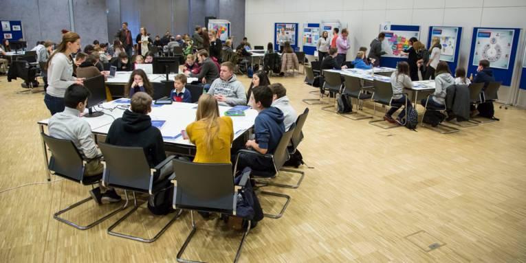 Im Veranstaltungssaal des Regionshausessind mehrere Tischinseln zusammengestellt, an denen Gruppenarbeit stattfindet. Im Hintergrund stehen Stellwände mit Informationen.