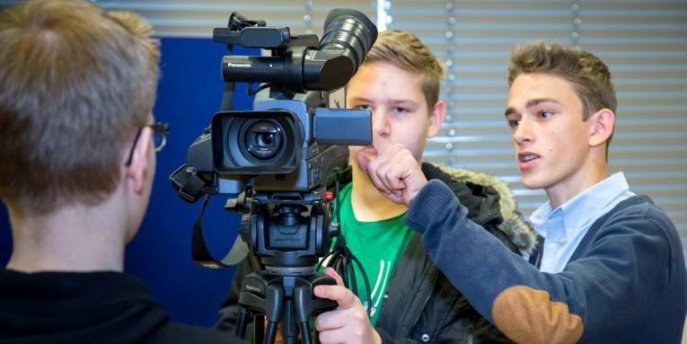 Zwei Schüler und ein Experte (rechts) beschäftigen sich mit einer Kamera, die auf einem Stativ steht.
