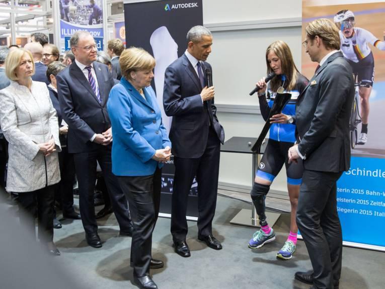 Frau mit Beinprothese zeigt anderen Leuten ein Bauteil.