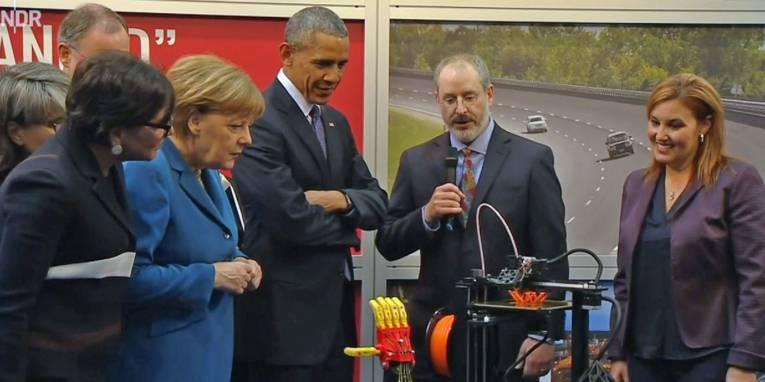 Mann zeigt anderen Menschen ein technisches Gerät.