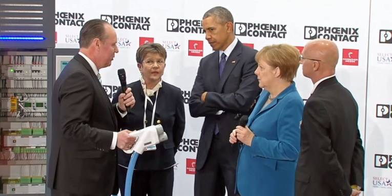 Mann zeigt anderen Leuten einen großen Elektrostecker