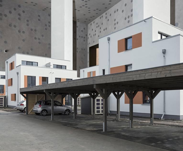 Gebäude mit Holzüberdachung davor, unter der ein Auto parkt.