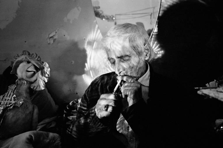Alter Mann zündet sich eine Zigarette an.