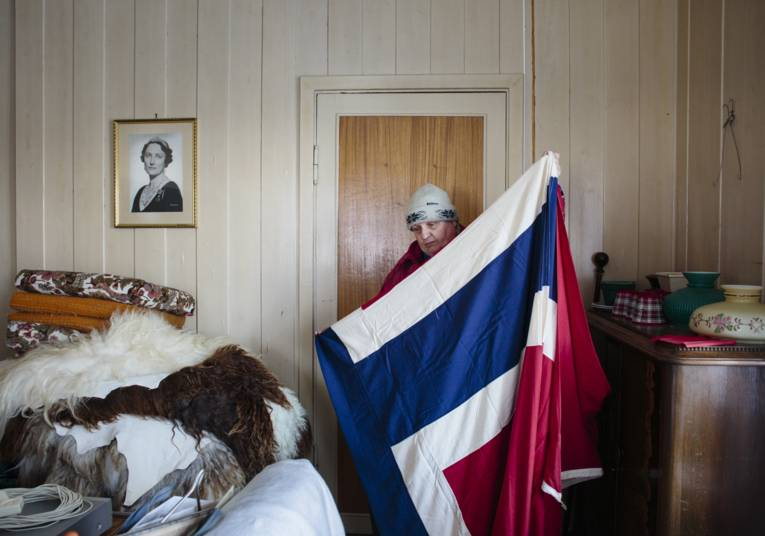 Frau steht in einem Schlafzimmer und hält eine Landesflagge in den Händen.