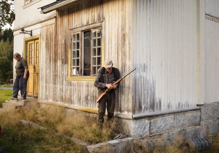 Alter Mann mit einem Gewehr und alte Frau vor einem Holzhaus.