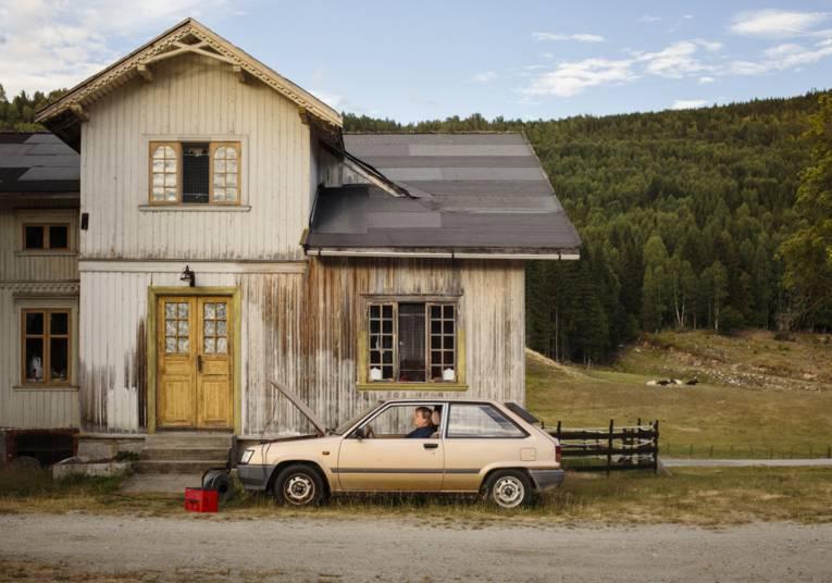 Person in einem Auto vor einem Holzhaus