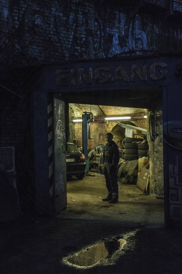 Mann steht in einer Garage