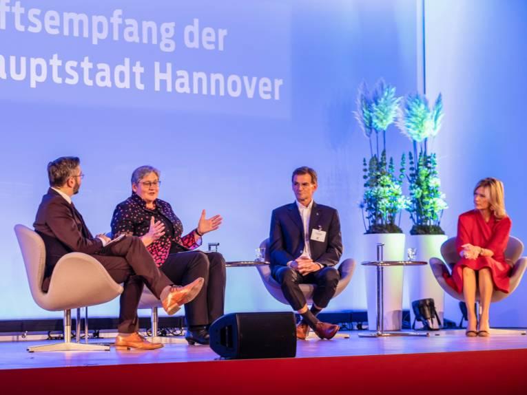 Vier Personen sitzend auf einer Bühne im Gespräch