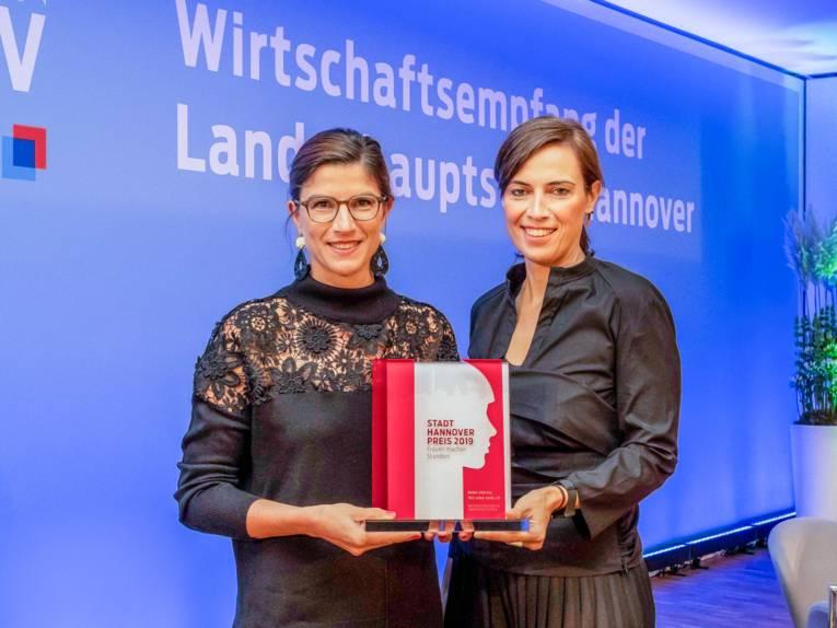 Zwei Frauen, die eine Auszeichnung in den Händen halten