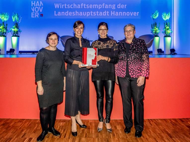 Vier Frauen vor einer Bühne