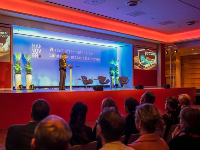 Eine Frau steht auf einer Bühne und hält einen Vortrag