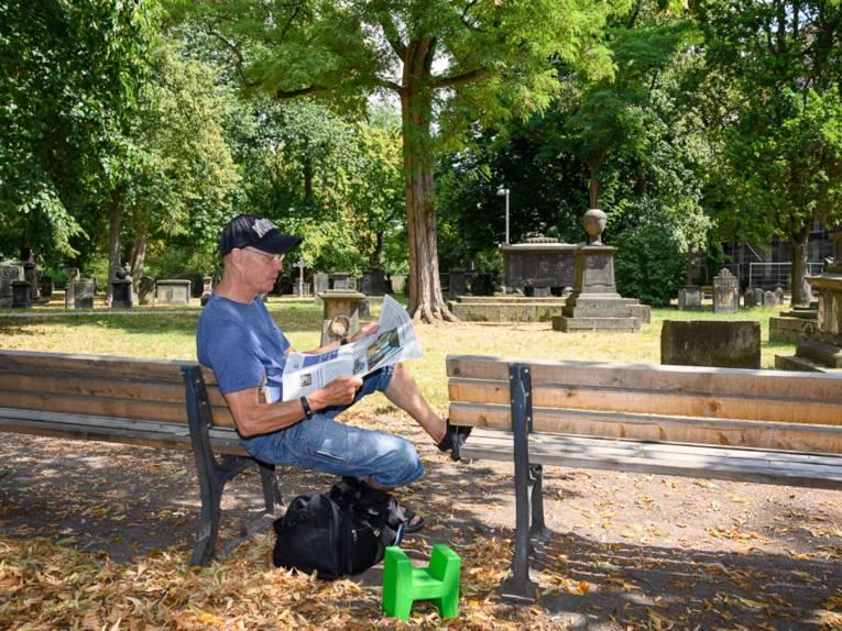 Eine Person mit einer Zeitung auf einer Bank im Grünen.