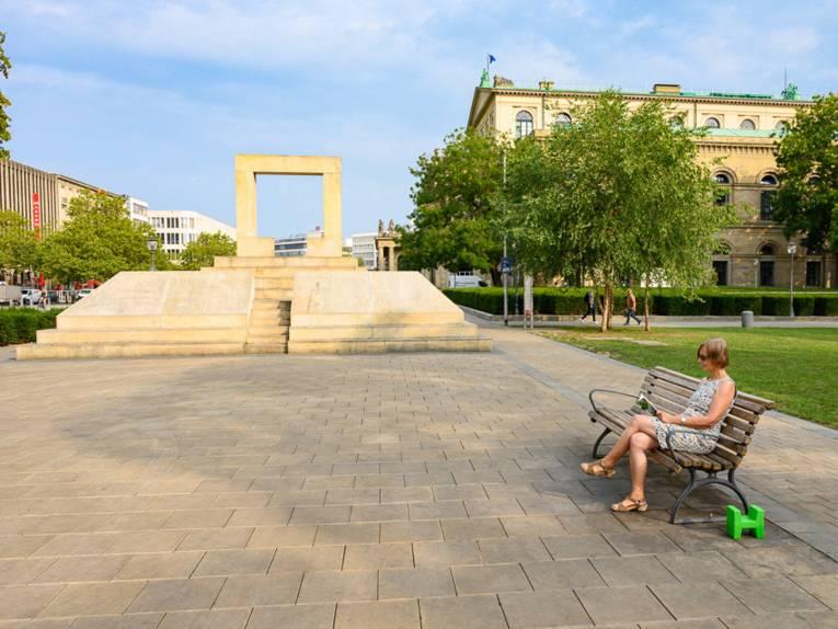 Person auf einer Bank auf einem Platz.
