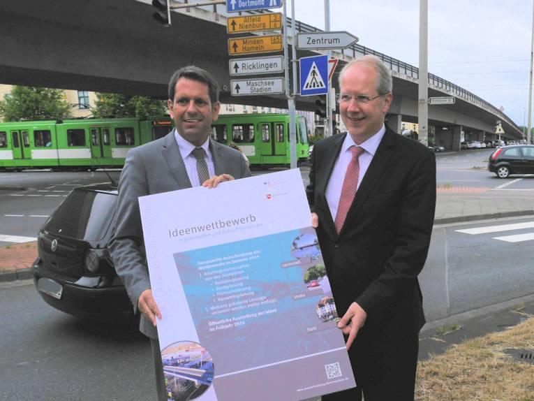 Zwei Männer in Anzügen halten ein Plakat hoch.