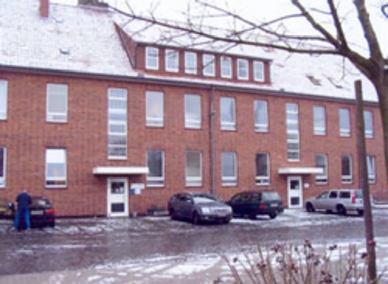 rotes Klinkergebäude mit Schee auf dem Dach und Schneeresten auf der Straße, vor dem Gebäude parken vier Autos, am Wagen links außen steht ein Mann mit dem Rücken zum Betrachter