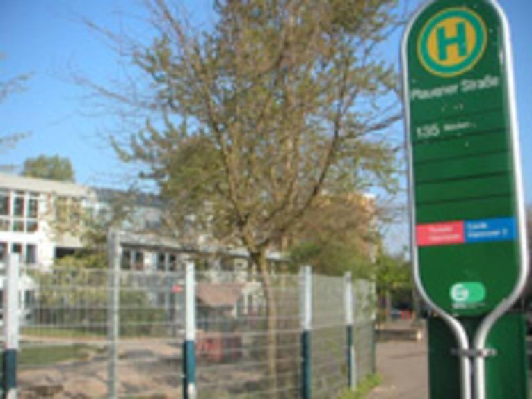 Im Vordergrund grüner Haltestellenmast der Üstra für die Buslinie 135, im Hintergrund das Gebäude mit Zaun davor