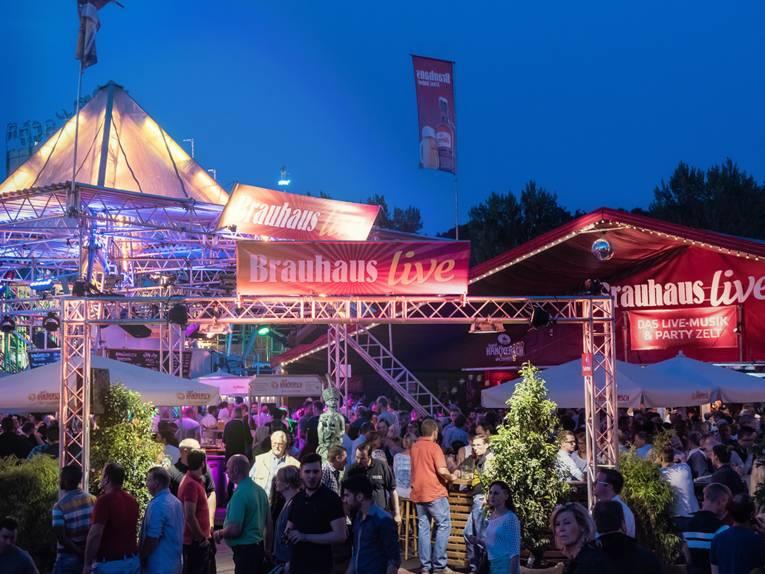 Festzelt und Eventbereich voller Menschen am Abend.
