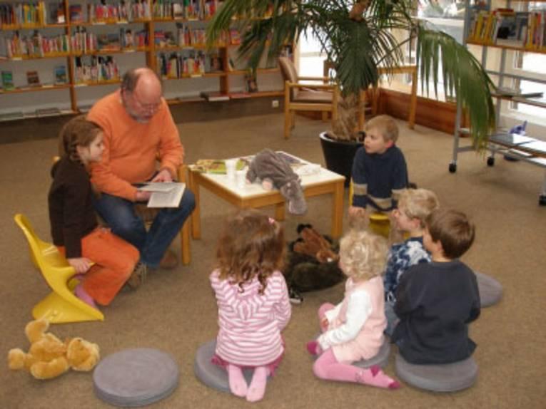 Ein Erwachsener liest kleinen Kindern vor
