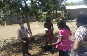 Vier Personen begutachten auf dem Schulglände der Makalanga Primary School eine mögliche Pflanzfläche.