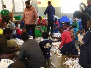 Schüler*innen in einem Klassenraum mit Papierschnipseln auf dem Boden.