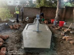 Bauarbeiter bei der Fertigstellung eines Brunnens mit Handpumpe