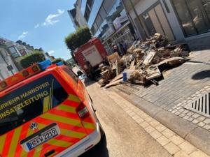 Ein Auto der Feuerwehr Hannover und ein Auto der Feuerwehr Euskirchen vor zerstörtem Mobiliar