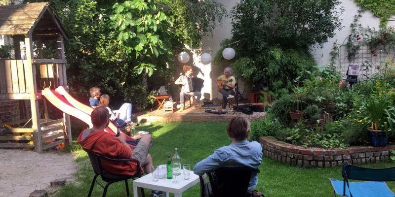 Menschen sitzen in dem Garten eines Hinterhofs und folgen dem Konzert von zwei Musikern.