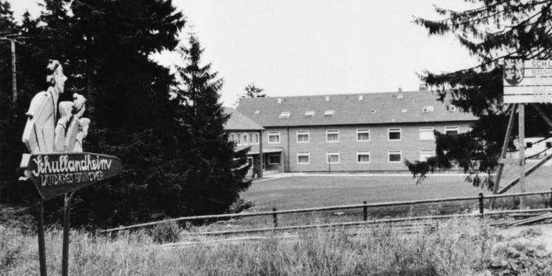 """Schwarz-Weiß-Fotografie: Wegweiser mit geschnitzten Köpfen und dem Text """"Schullandheim Torfhaus"""", im Hintergrund ist ein Gebäudekomplex zu sehen."""