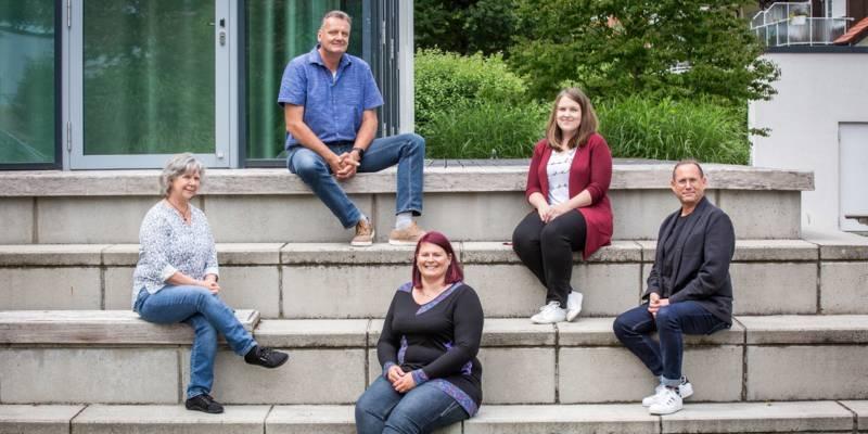 Drei Frauen und zwei Männer sitzen unter freiem Himmel mit großem Abstand auf einer Treppe.