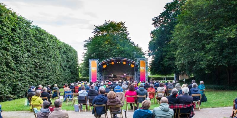 Publikum verfolgt das Programm auf einer kleinen Bühne im Grünen.