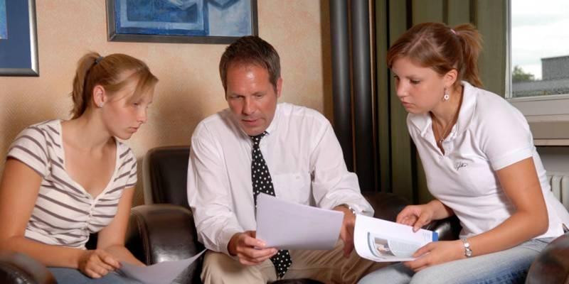 Zwei Frauen schauen auf die Hände eines Mannes, er zeigt etwas auf einem Papier. Die Szene findet in einer Sitzecke mit Ledersesseln statt.