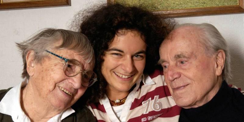 Eine junge Frau, die rechts im Arm eine Seniorin hält und links im Arm einen Senior. Hinten an der Wand sind Teilstücke zweier Gemälde zu sehen.