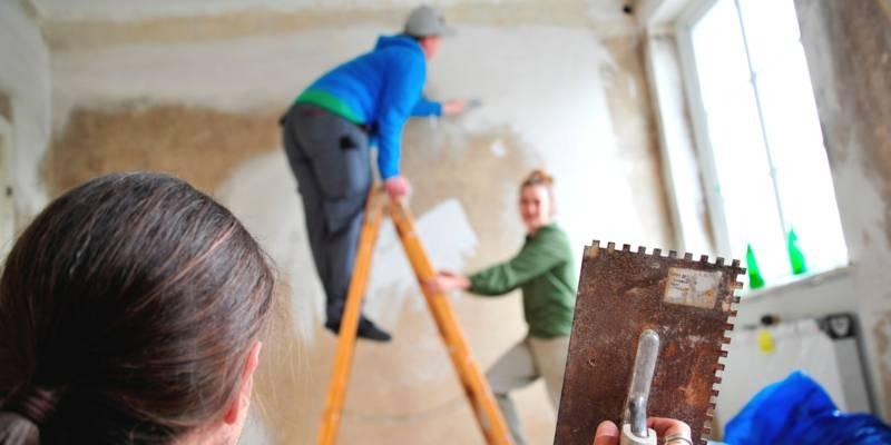 Ein Mann hält eine Kelle zum Verputzen in der Hand. Im Hintergrund stehen eine Mann und eine Frau auf einer Leiter und verputzen eine Wand.