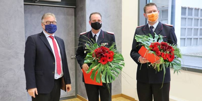 Drei Männer stehen nebeneinander, sie halten Abstand und tragen Mund- Nasen-Bedeckungen. Die zwei Männer neben Regionspräsident Hauke Jagau tragen den Dienstanzug der Freiwilligen Feuerwehr.