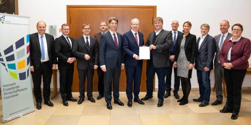 Zehn Männer und zwei Frauen tragen Anzüge und ähnliche Geschäftskleidung, zwei Männer in der Bildmitte halten eine Urkunde.