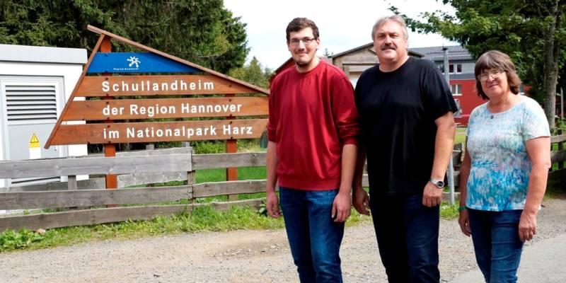 """Zwei Männer und eine Frau stehen vor dem Schullandheim Torfhaus, auf einem Schild steht """"Schullandheim der Region Hannover im Nationalpark Harz""""."""