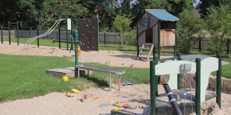 Rutschenturm mit Kletterwand, Wasserpumpe und weitere Spielgeräte auf einem Kinderspielplatz.