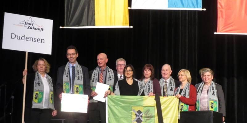 Personen stehen auf einer Bühne, sie halten unter anderem ein Ortsschild und eine Fahne.