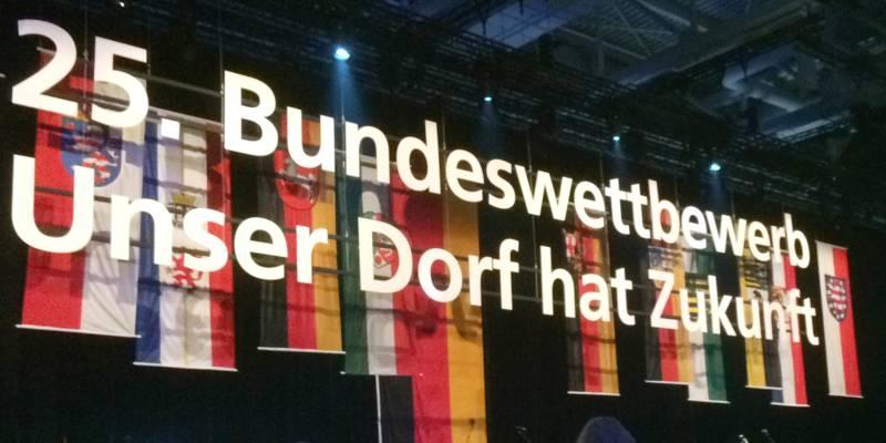 Fahnen der deutschen Bundesländer schmücken eine Bühne.