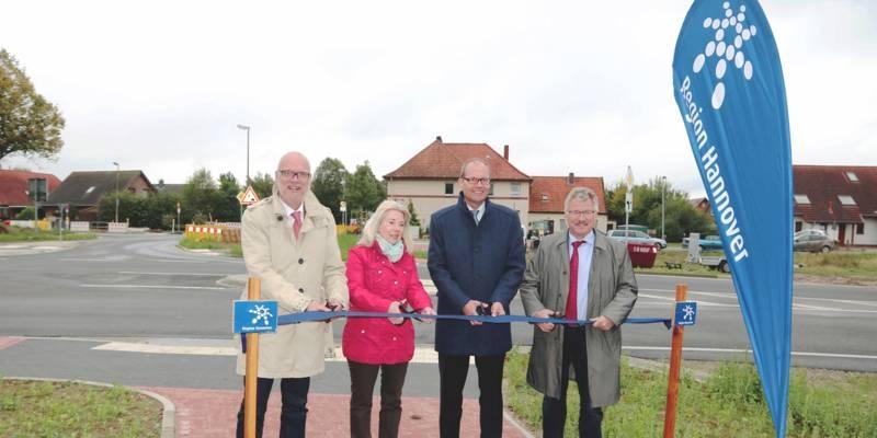 Drei Männer und eine Frau stehen hinter einem blauen Band, das sie symbisch mit Scheren durchschneiden. Hinter ihnen ist eine neue Straße.