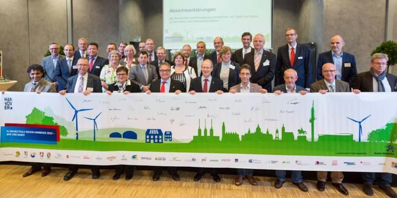 Gruppenfoto mit vielen Personen. Die erste Reihe hält ein sehr breites Banner.