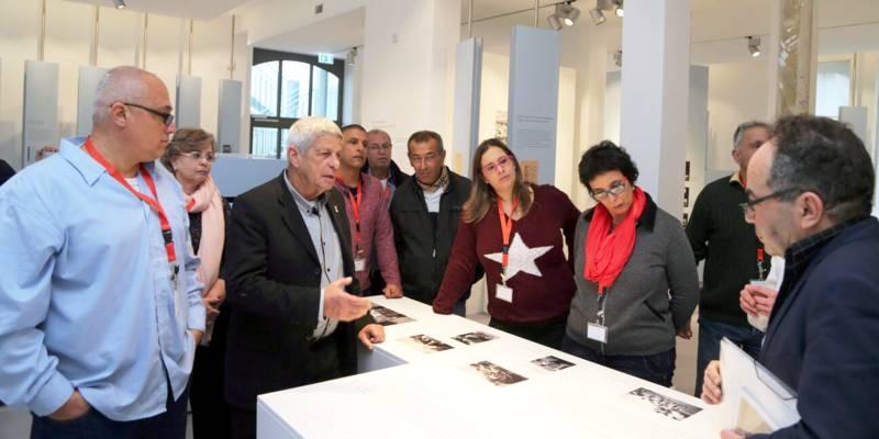Zehn Personen schauen auf Ausstellungsstücke in der Gedenkstätte Ahlem