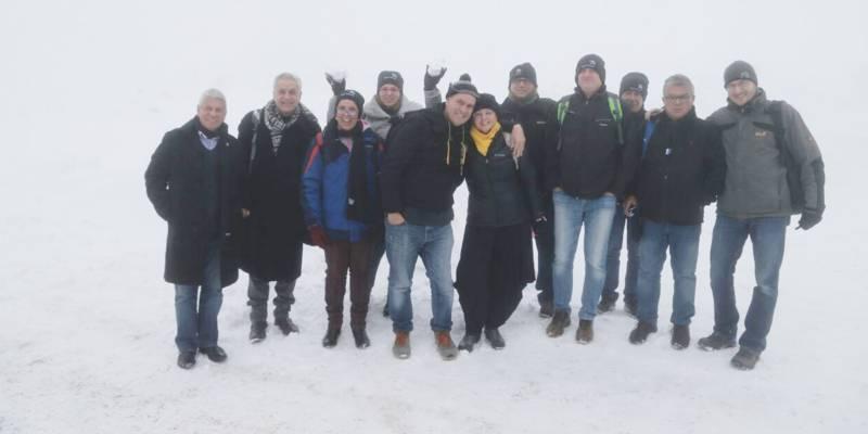 Elf Personen stehen im Schnee