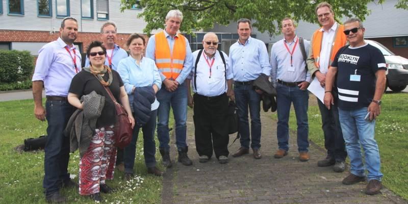 Zehn Personen haben sich für ein Foto nebeneinandergestellt, zwei Männer tragen Warnwesten.