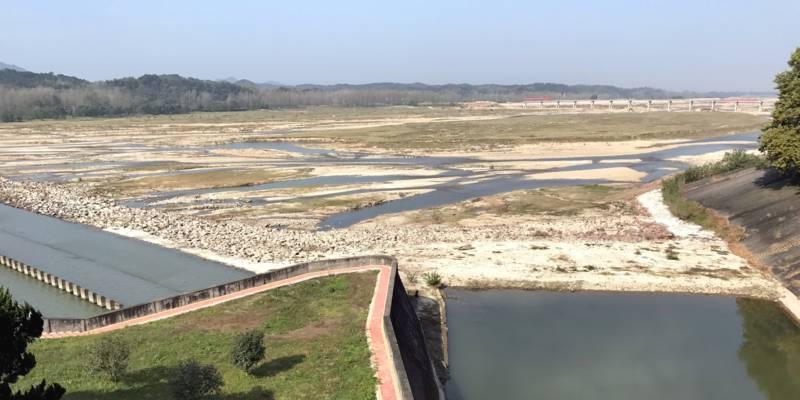 Blick auf das Innere eines Staudamms, die Wasserfläche ist von Sandboden unterbrochen.