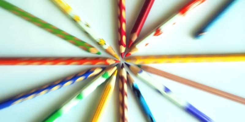 Buntstifte verschiedener Farben liegen auf einen weißen Blatt Papier, durch den Reiss-Zoom-Effekt sind nur die Spitzen scharf.